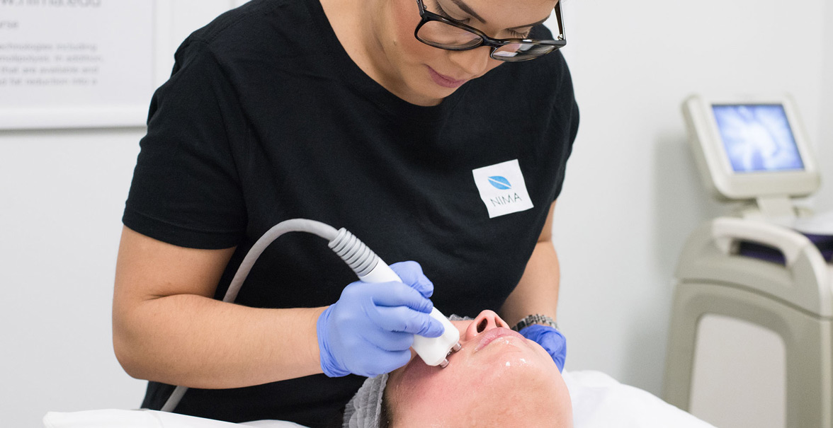 An aesthetician performing a procedure on a patient.